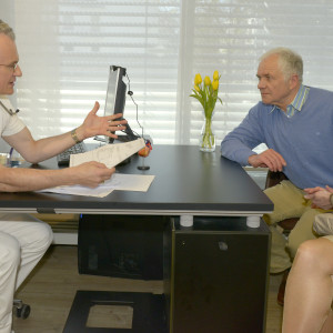 male-medical-professional-talking-with-couple-in-consulting-room-300x300